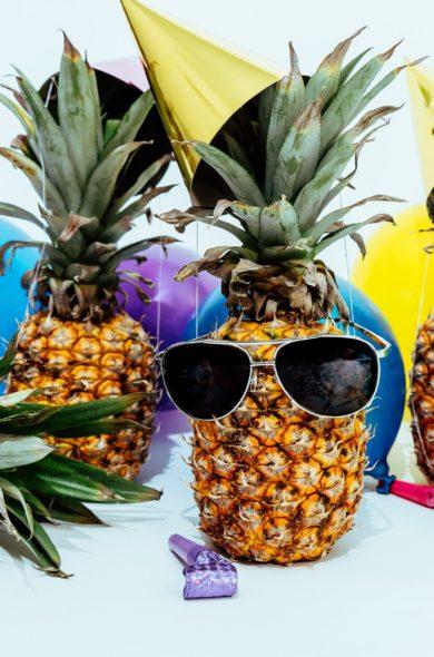 Ananas mit Partyhüten und Luftballons