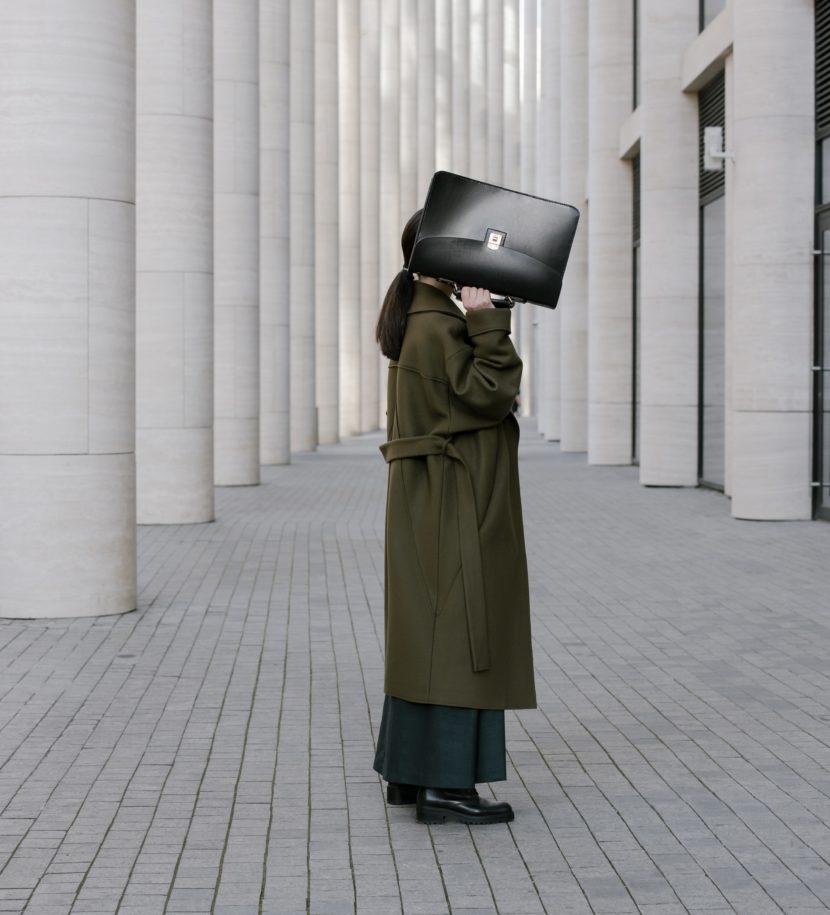 Frau hält sich Aktentasche vors Gesicht