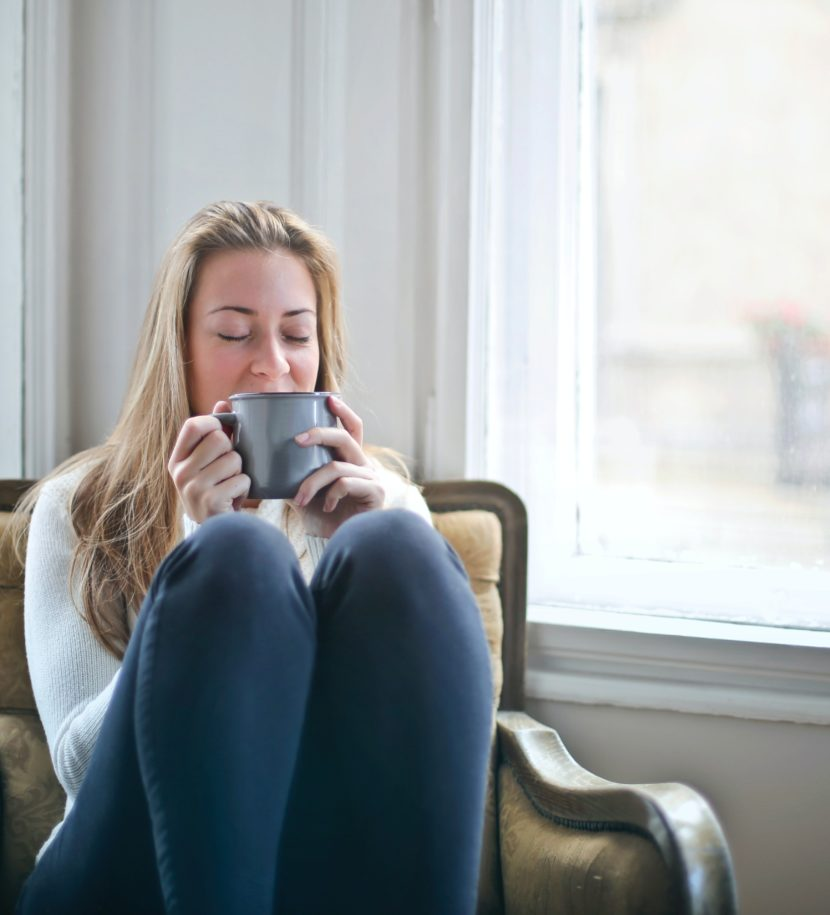 Frau mit Kaffeetasse in gemütlichem Stuhl