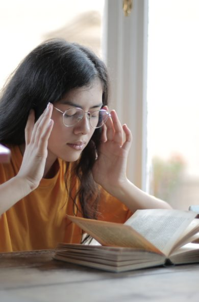 Frau am Schreibtisch liest ein Buch