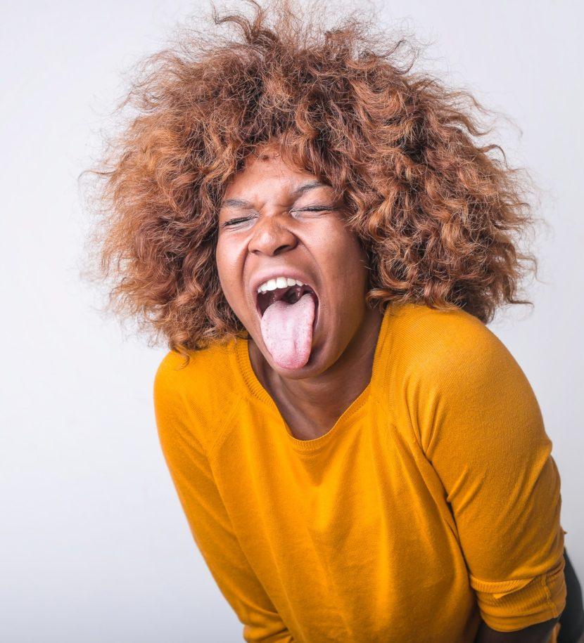 Frau mit Wuschelkopf streckt die Zunge raus