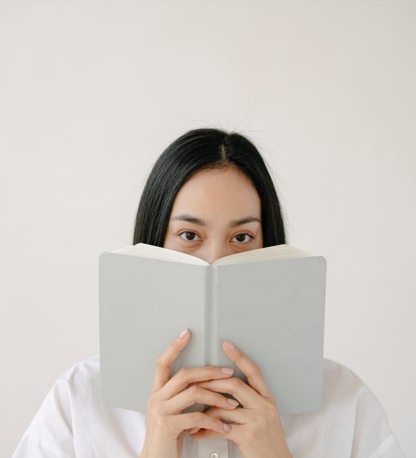 Frau hält Buch vors Gesicht